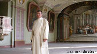 Adminstrator Father Augustin in the former dining hall. Paintings and rich ornaments decorate the walls and ceiling.