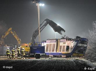 Einsatzkräfte bergen mit Kranwagen nachts den verunglückten Triebwagen (Foto: dapd)