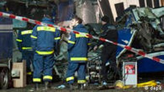 Das Technische Hilfswerke zerlegt mit Hilfe eines Baggers den Personenzug (Foto: dapd)