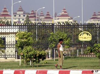 A local man walks past the fence outside the parliament building in Naypyitaw, Myanmar