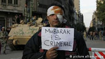 a wounded protester holds up an anti-Mubarak sign