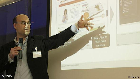 A man, giving a presentation, points to an image on a big screen