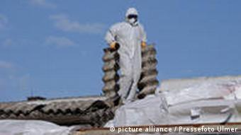 Rottenburg (Kreis Tuebingen) 28.20.2010 Ein Arbeiter entfernet mit Schutzanzug und Mundschutz, Eternitplatten von einem Dach einer Industriehalle. FOTO: Pressefoto ULMER/Markus Ulmer