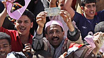 A Yemeni demonstrator displays a local currency note