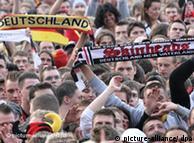 Jovem exibe uma faixa com dizeres extremistas em meio a torcedores da seleção alemã