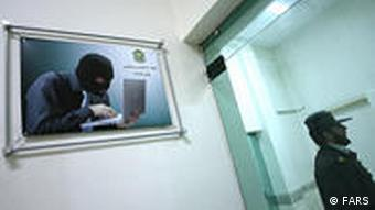 A picture of masked person using a computer hangs on the wall inside an office of the Iranian cyber police