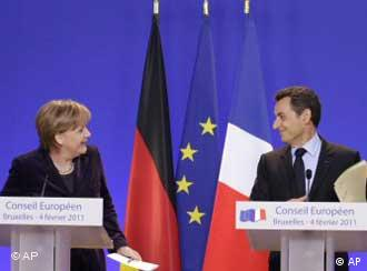 French President Nicolas Sarkozy (r) looks at German Chancellor Angela Merkel