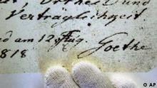 Die Finger einer Archivarin des Goethe Schiller Archivs zeigen am Dienstag, 24. September 2002 die Originalunterschrift Johann Wolfgang v. Goethes unter einem Schriftstueck aus dem Westoestlichen Divan. Der handschriftliche Nachlass Goethes, welcher 400 Archivkaesten umfasst, wird am Dienstag ins UNESCO Weltkulturerbe aufgenommen. (AP Photo/Christian Seeling)