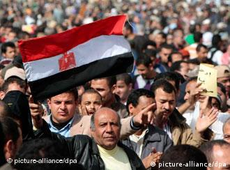 A protestor waves the Egyptian national flag during a protest in Tahrir Square