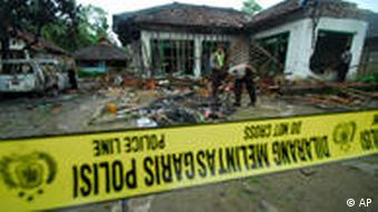 Police officers inspect the damaged house of a member of Ahmadiyah after it was attacked by Muslim mob in Pandeglang, Banten province, Indonesia, Monday, Feb. 7, 2011. The machete-wielding mob on Sunday attacked the home of the minority sect leader in central Indonesia, killing three and wounding six others, police and witnesses said. (AP Photo)