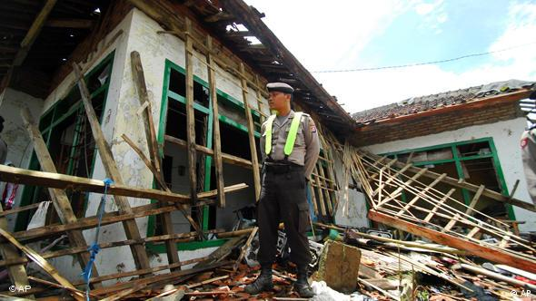A police officer stands guard at the damaged house of a member of the Ahmadiyah after it was attacked by a Muslim mob