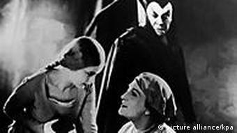 Eine Szene aus einer Faust-Aufführung aus den 1920er Jahren mit Gretchen (links), Faust (rechts) und Mephisto (hinten)