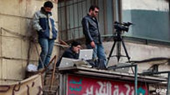 A camera crew standing on a building overlooking Tahrir Square.