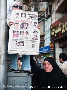 Holding the newspaper with his picture, a woman weeps the death of her son