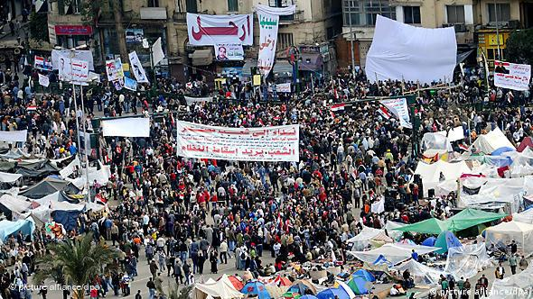 Egyptian protesters hold banners at Tahrir Square