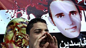 An Egyptian protester in front of a banner showing pictures of Said alive and his corpse