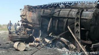 An Afghan policeman stands near a burned out oil tanker