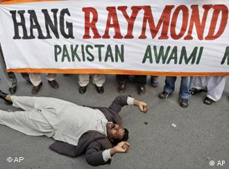 A Pakistani demonstrator lays on the ground while others hold a banner during a rally against Raymond Davis