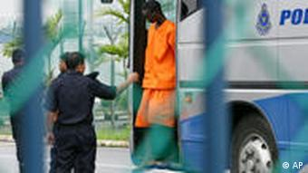 A Malaysian police officer brings out an accused Somali pirate from a bus