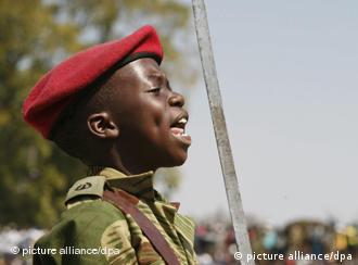 ARCHIV - Ein zwölfjähriger Junge mit Waffe und Uniform bei einem Appell in Simbabwes Hauptstadt Harare am 11.08.2009. Der 10. Februar ist der Internationale Tag der Kindersoldaten. Er soll an die rund 250 000 Kinder und Jugendlichen erinnern, die von Warlords in den Krisenregionen Afrikas und anderen Konfliktgebieten zum Kämpfen und Töten gezwungen werden - Opfer und Täter zugleich. Foto: EPA/AARON UFUMELI (zu dpa-Korr vom 09.02.2011) +++(c) dpa - Bildfunk+++