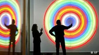 A gallery owner points to the piece Target by artist John M Armleder as a visitor looks on