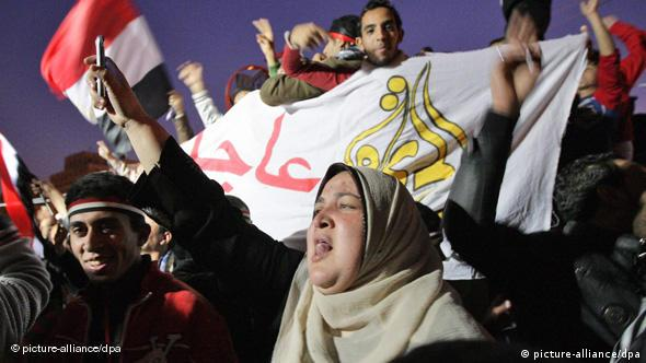 Egyptian protesters cheer, waving flags and banners