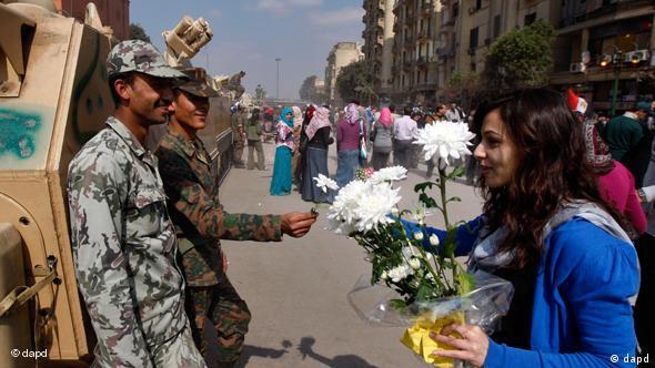 Eine Ägypterin überreicht Blumen an zwei Soldaten auf dem Tahrir-Platz in Kairo (Foto:AP)