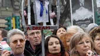 Women hold a poster with a photo of Italian premier Silvio Berlusconi behind bars