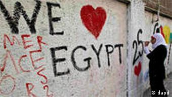 A woman paints 'we love Egypt' on a wall in Cairo