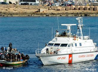 Ein offenes Boot voller Menschen und ein weißes Schiff. (Foto: dapd)