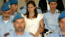 American murder suspect Amanda Knox, center, is escorted by Italian penitentiary police officers from Perugia's court after a hearing, central Italy, Tuesday Sept. 16, 2008. A judge in Perugia is leading a hearing Tuesday on a request for trial for Knox and two other suspects in the 2007 slaying of British student Meredith Kercher in this university town in Umbria. Suspect Amanda Knox, who is from Seattle, showed up in court, but her former Italian boyfriend Raffaele Sollecito did not. The third suspect, Rudy Hermann Guede, an African who lives in Perugia, was attending the hearing. All three deny wrongdoing. (AP Photo/Antonio Calanni)