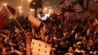 Bahraini anti-government protesters wave flags in a demonstration in Manama