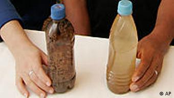 Indigenous leaders show bottles of polluted water from their communities