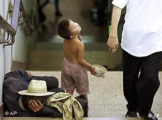 A Chinese boy begs in a subway while an adult homeless sleeps nearby in Beijing Sunday, July 7, 2002. Chinese escaping poverty in other provinces, sometimes bring their children to beg for them on the streets of Beijing. (AP Photo/Str)