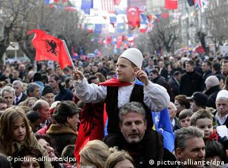 Child with Kosovo flag on father's shoulders