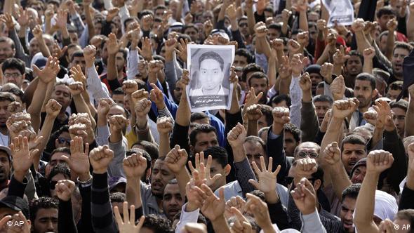 Teilnehmer eines Trauermarsches strecken ihre Fäuste und Bilder des Getöteten in die Höhe (Foto: AP)