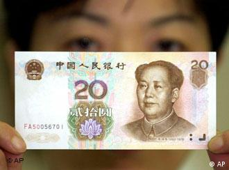 ** ADVANCE FOR TUESDAY, DEC. 26 ** A bank clerk shows a new 20 renminbi (then 2.40 U.S. dollars) note, bearing a portrait of Mao Zedong, founder of the People's Republic of China, Oct. 20, 2000 at Bank of China in Shanghai. The new note started circulating Oct. 16 officially to replace old 1 and 2 renminbi notes. Was Mao a monster or an authentic Chinese hero? Historians, journalists and many Chinese are still pondering these questions at the 113th anniversary of the birth of Mao, father of communist China. Mao was born on Dec. 26, 1893. (AP Photo/Eugene Hoshiko)