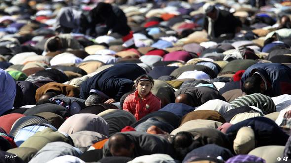 A girl looks up as thousands pray during Friday prayers in Tahrir square in Cairo, Egypt, Friday Feb. 18, 2011. (AP Photo/Khalil Hamra)