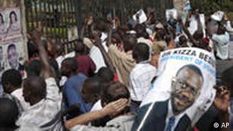 Anhänger von Kizza Besigye halten dessen Porträt in Händen (Foto: AP)