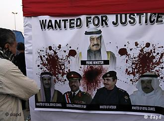 A Bahraini anti-government protester looks at a banner showing Bahraini prime minister Shiek Khalifa bin Salman Al Khalifa, top, and other Bahraini officials at the Pearl roundabout in Manama, Bahrain