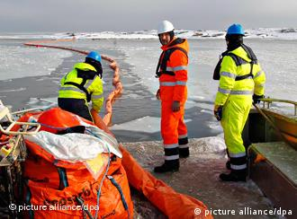 Clean-up crew members set up swimming oil barriers off the island of Sando to contain the Godafoss leak