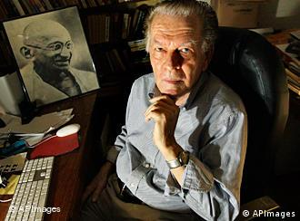 Gene Sharp sitting in his office in Boston, with a photo of Ghandi on his desk    Copyright: AP Photo/Elise Amendola