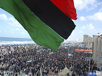 a scene from recent days' unrest in Benghazi with a Libyan flag