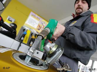 An Eni gas station worker fills a motorbike tank in Milan, Italy