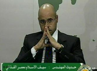 Seif al-Islam, son of Moammar Gadhafi, sits with hands pressed together giving an address on Libyan state television