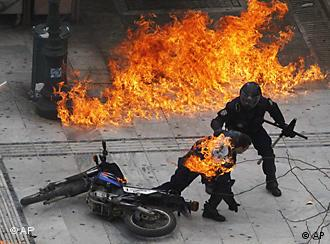 A policeman tries to help a colleague hit by a firebomb