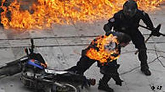 A motorcycle policeman burns as his colleague tries to help him after protesters threw a petrol bomb