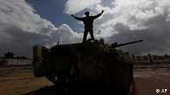 Moammar Gadhafi man in front of tank