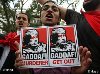 protester holding poster demanding that Gadhafi leave