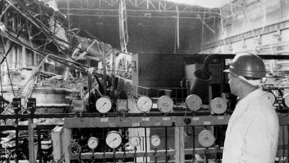 Rechts vorne sieht man einen Mann mit Schutzhelm in einem weißen Schutzanzug, dahinter eine zerstörte Halle und diverse Messinstrumente